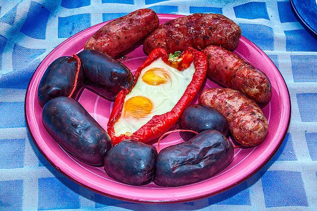 Plato con morron asado co dos huevos rodeados de chorizos y morcillasa