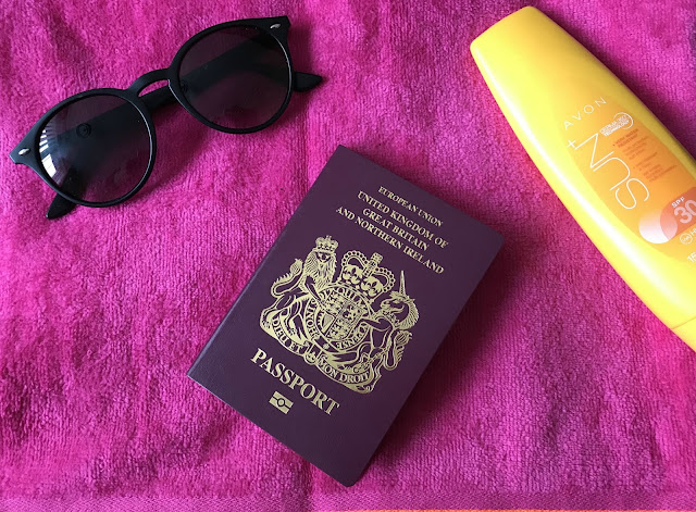pink beach towel, passport, sunglasses and sun lotion
