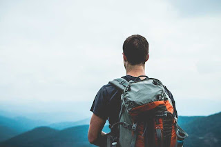Man with a backpack facing mountains