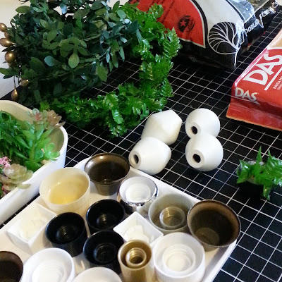 A tray of various bottle caps, a tray of various bit of plastic plant, two wreaths of leaves, a bag of modelling scenic material and a block af DAS air-drying clay arranged on a cutting mat.