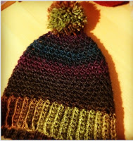 "A beanie made in February 2014, made of Bouvardia yarn in ""Shadow Spectrum"" colours. The pom pom and ribbing are light green and the body is in dark purple and turquoise colours."