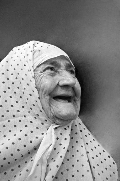 Beautiful black and white photo of an old lady wearing dotted scarf looking up and smiling