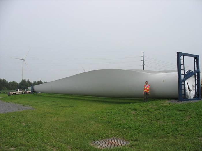 Human next to wind turbine blade
