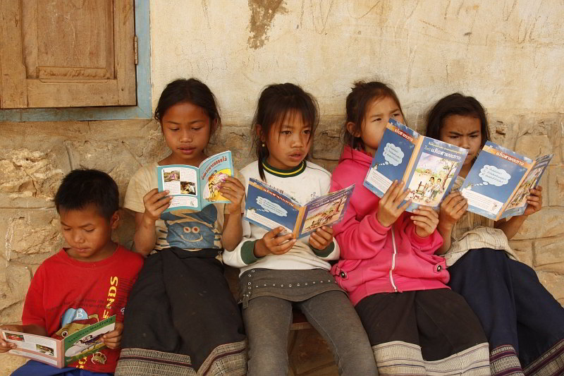 Lao children reading their first book at a Big Brother Mouse book party at their village school