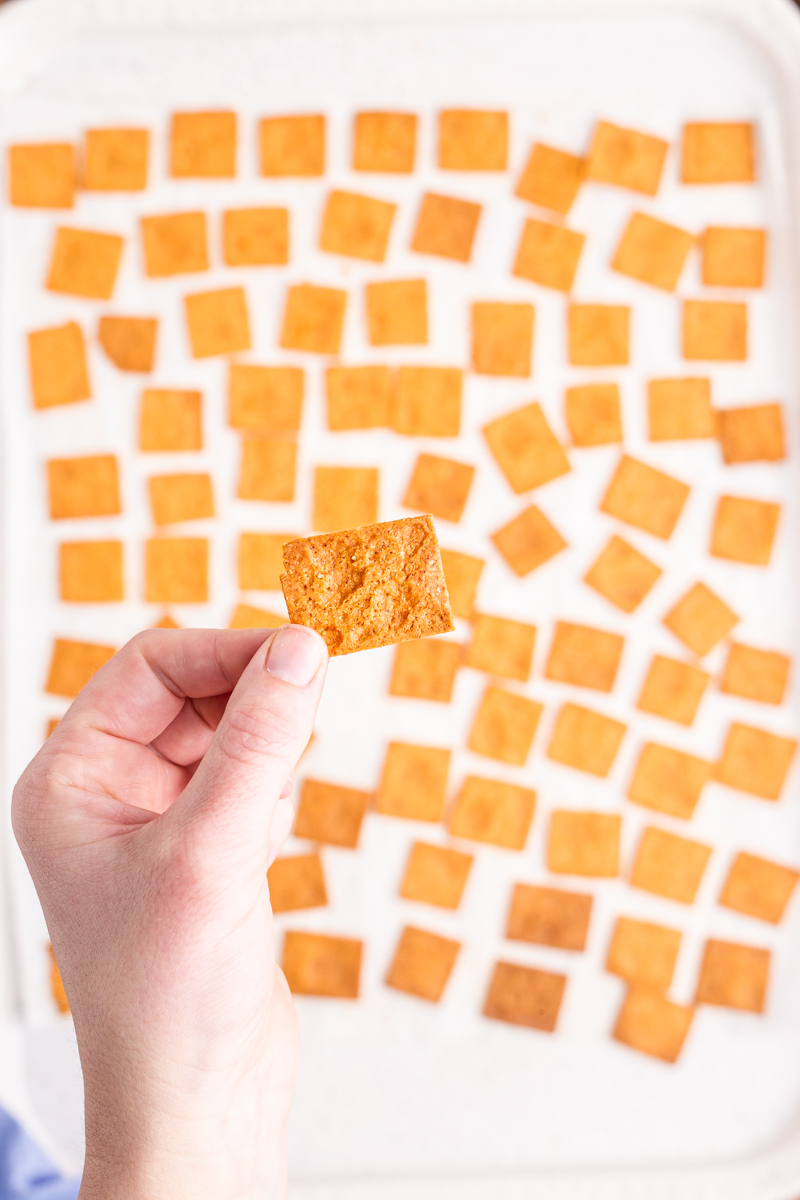 Closeup photo of someone holding a Keto Smoked Cheddar Cracker (Cheez-It) in their hand above a baking sheet covered in the crackers.