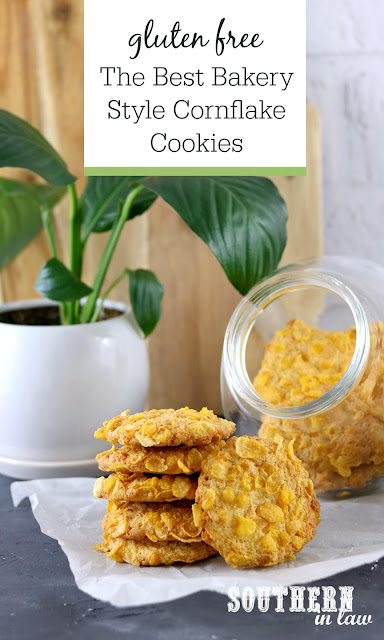 The Best Bakery Style Cornflake Cookies Recipe - Classic cornflake cookies in a stack in front of glass cookie jar in white kitchen
