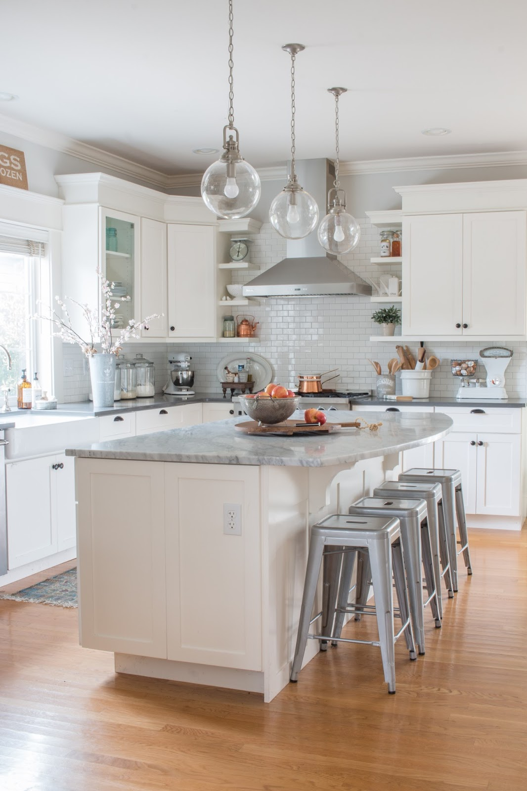 white kitchen cabinets, wood floor, and copper and farmhouse accents