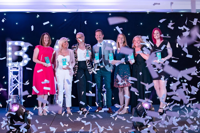 Photo of 7 bloggers on a stage, holding awards, with tickertape floating around everywhere. Steph is far left in a pink dress
