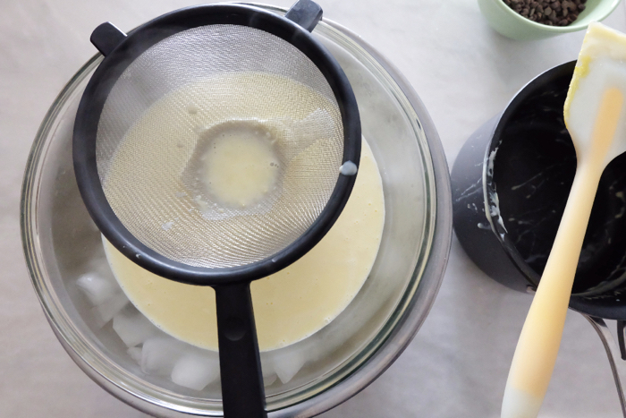 straining the custard through a sieve