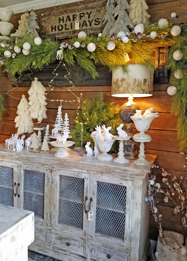 White winter wonderland mantel with greenery and white garland and white little trees>