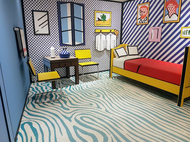 Image shows a full size Roy Lichtenstein Inspired Room Featuring a bed, table, chairs, mirror, window, items of clothing, jug and milk carton. There is also a lichtenstein inspired van gogh self portrait on the wall. It appears like a picture but is an actual room.