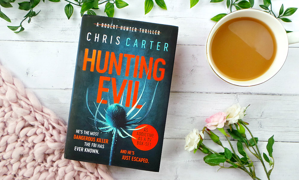 The hardback book Hunting Evil is on a table with some leaves, a pink chunky knit blanket and a cup of tea. The cover of the book is blue with orange text and shows a thistle