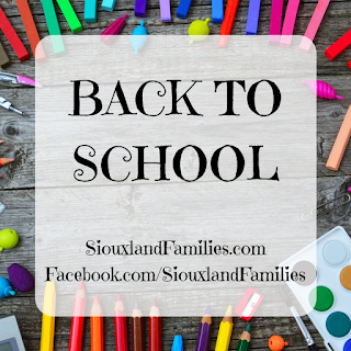 """in background, brightly colored school supplies on a gray wood slat table. in foreground """"back to school"""" and """"SiouxlandFamilies.com Facebook.com/SiouxlandFamilies"""""""