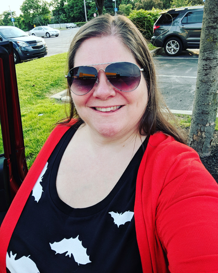 image of me from mid-chest up, standing in a parking lot, wearing aviator sunglasses, a red cardigan, and a black t-shirt with white bats on it