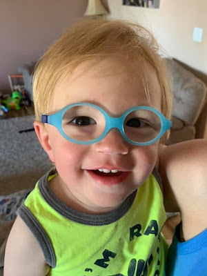 Headshot of smiley Kadyn Lucas, 1 year old, showing off his new eyeglasses