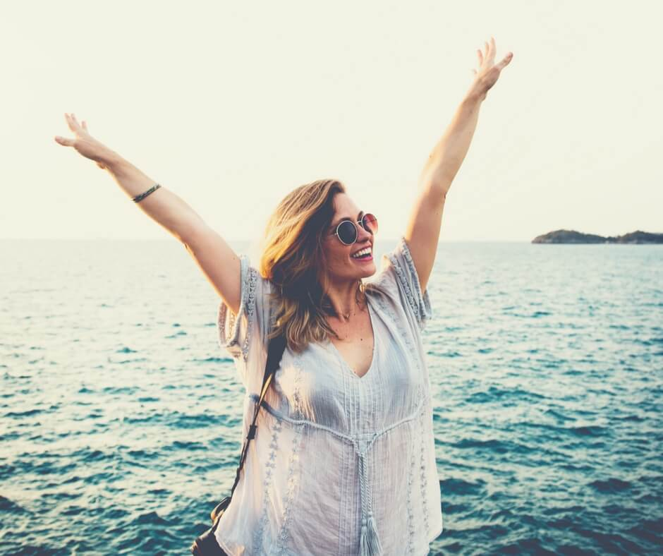 woman reaching her arms up into the air. She is smiling, wearing sunglasses. She stands on rocks by the ocean.