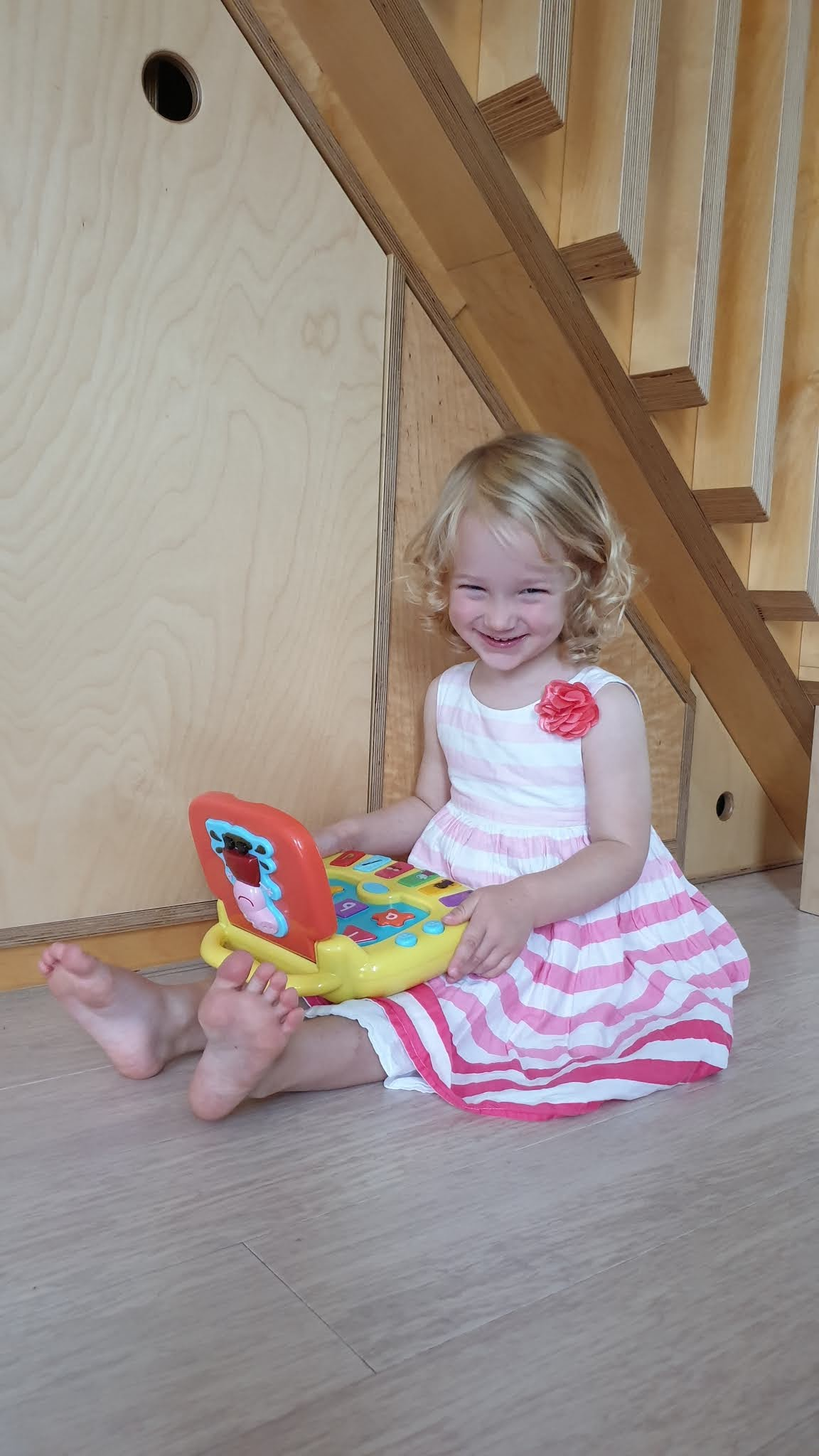 toddler smiling with a peppa pig laptop