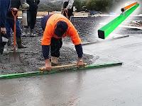 Bir işçi yeni dökülmüş bir beton yüzeyini mastarla düzleştirirken
