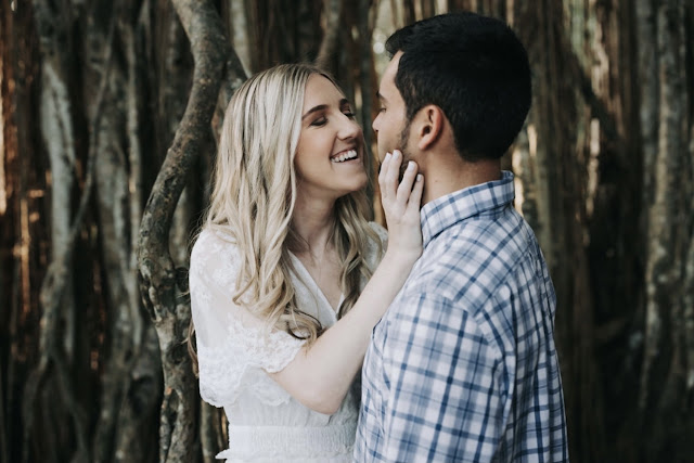couple smiling in front of trees