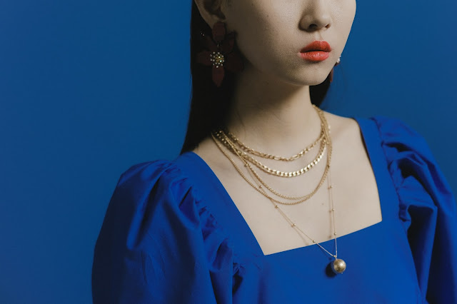 Asian female wearing a blue dress and a variety of jewelry.