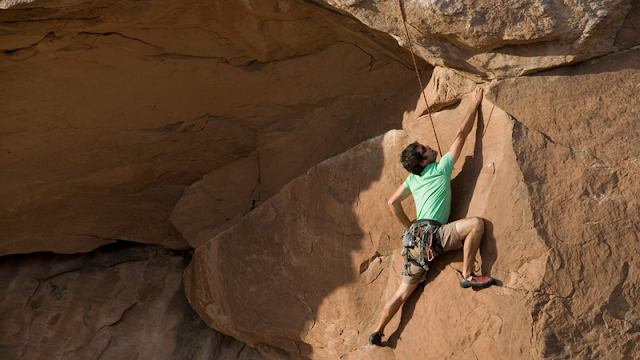 a top rope climber on a nearly flat rock face