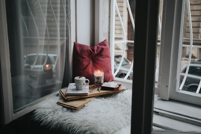 A window seat with comfy blankets, a mug and a candle