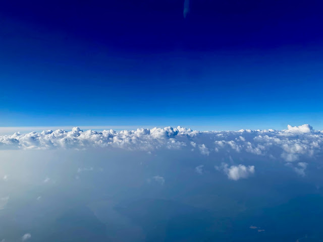 A view from a plane, with sculpted clouds below and an impossibly blue sky above.