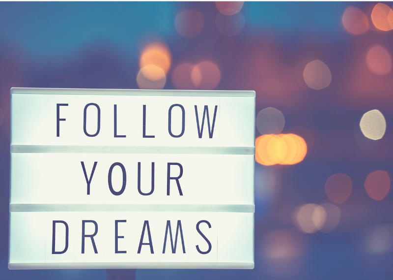 "A sign saying ""Follow your dreams"" in a post about why you should regularly review your goals"