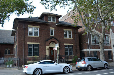 Two story red brick house on church property