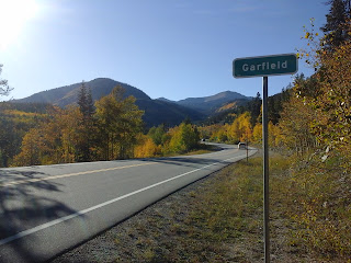 Beautiful fall day with sunshine along Monarch Pass, next to the Garfield highway sign.