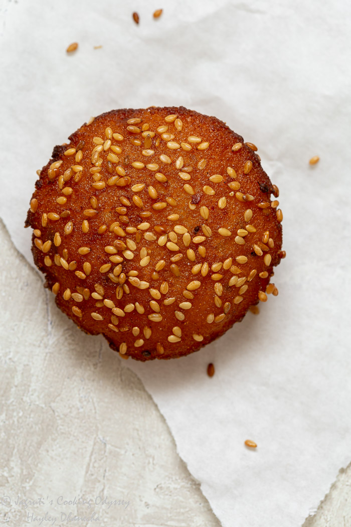 A single piece of Methi makai na dhebra or vada on white parchment paper.