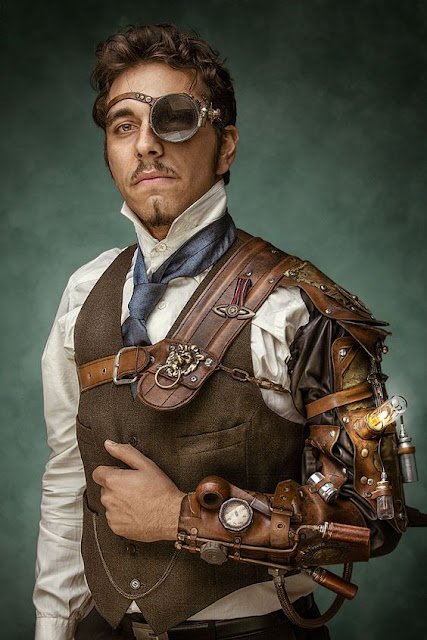 Man wearing Steampunk clothing. He wears a large glass monocle. Clothing: waistcoat/vest, high collar shirt, tie, and steam powered bracer/mechanical arm. Men's steampunk fashion.