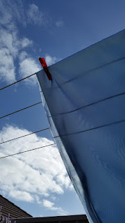 Blue satin hanging on the washing line, viewed from beneath. A blue sky with white clouds can be seen behind the satin. Other shapes in the background include the edge of a fence along the bottom, a roof ridge in the bottom left corner and also the tips of some lavender flowers in the bottom left foreground in front of the fence.