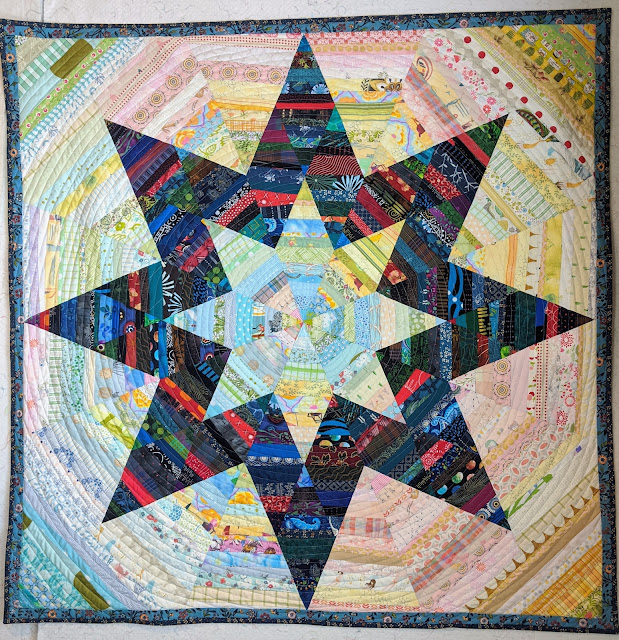 The finished quilt has a light eight pointed star in the center surrounded by 24 dark string pieced diamonds that form a larger eight-pointed star that rest on a background of more light strings.