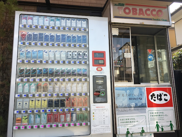 Picture of a cigarette vending machine and small windows selling tobacco goods attached to a new house