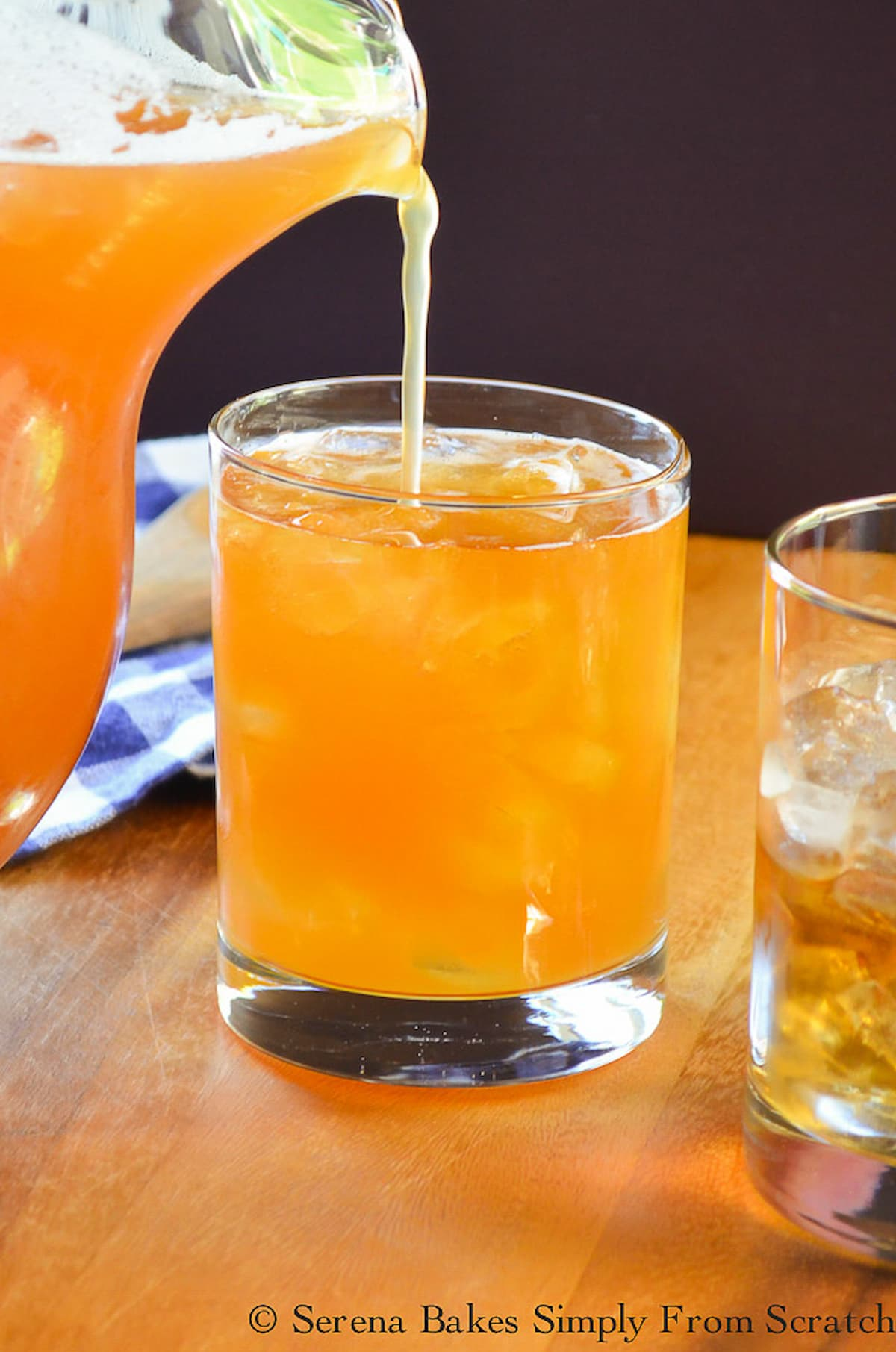 Peach Whiskey Iced Tea being poured from a pitcher into a glass filled with ice.