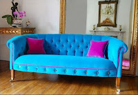 Arctic blue tufted velvet sofa with pink pillows