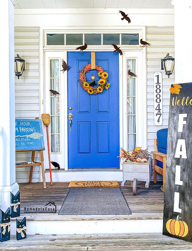 Black crows front porch with blue door and long Fall sign and sunflower wreath