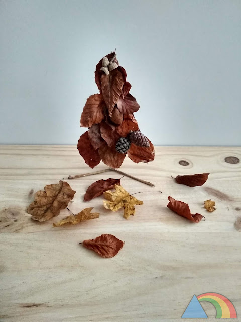 Árbol de otoño hecho con palitos y hojas, y decorado con capuchones de bellota y piñas
