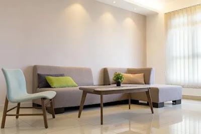 Imagem ilustrativa de uma sala de apartamento com sofá bege, cadeira branca ilustrando texto sobre sublocação