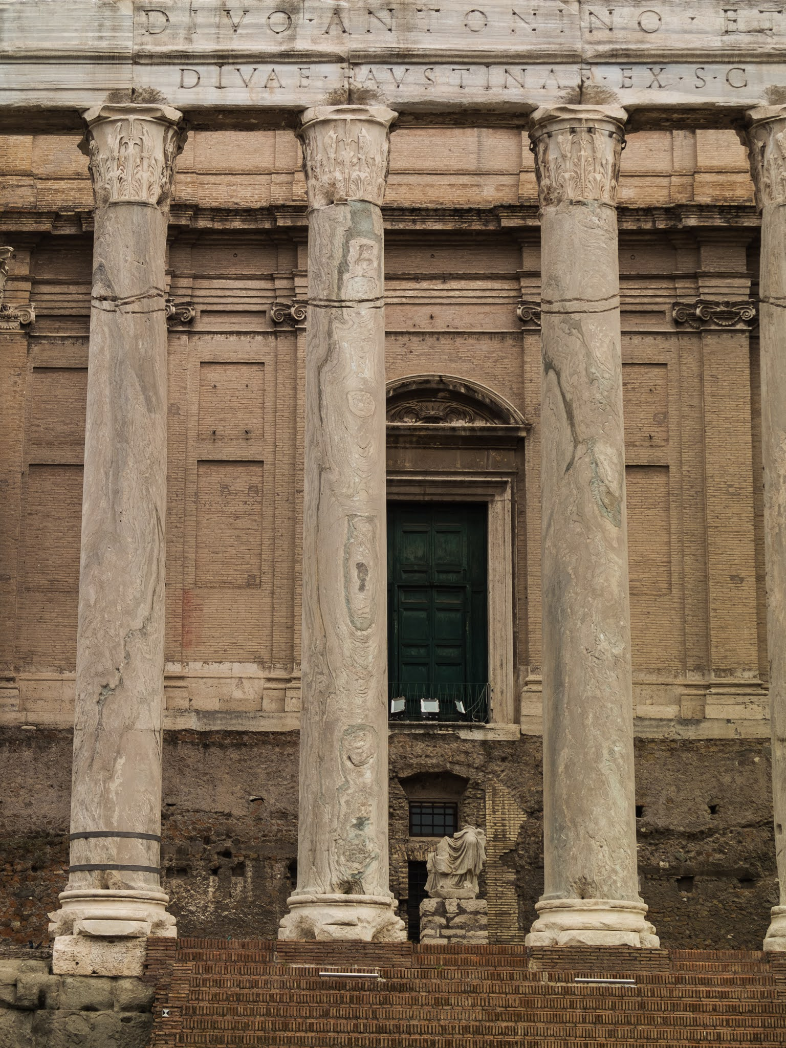Red brick steps, columns and green door of the Temple of Antoninus and Faustina in the Roman Forum.