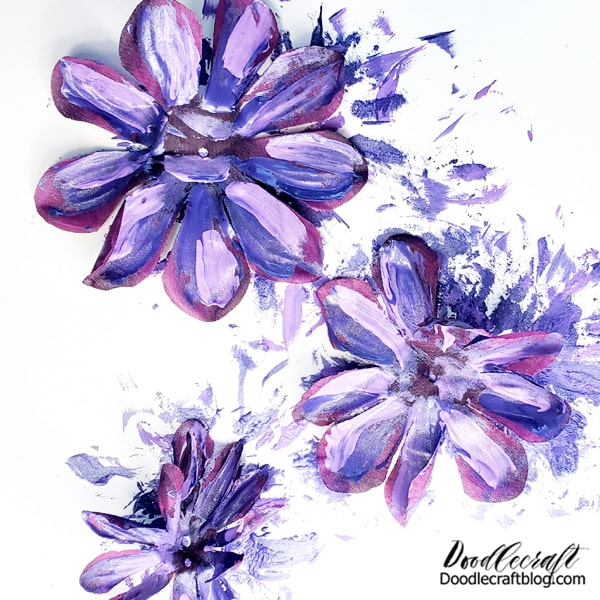 Lay the petals out on a disposable or washable surface and begin painting broad and messy strokes of your color scheme paint on the silk petals.  Step 2: Paint! **This is messy! The paint will bleed right through the petals and essentially paint both sides at once. This is a great way to make a Monet look that will match your decor.   Don't be too precious about painting them, just slab on some paint and move on.