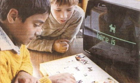 Two children using a TRS-80 concept keyboard to type fully formed words on a green-screen monitor. A blocky picture of a dog above a line, with the text here is, is displayed.