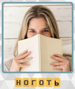 в руках девушки книга которой она закрывает лицо и видны ногти на руках