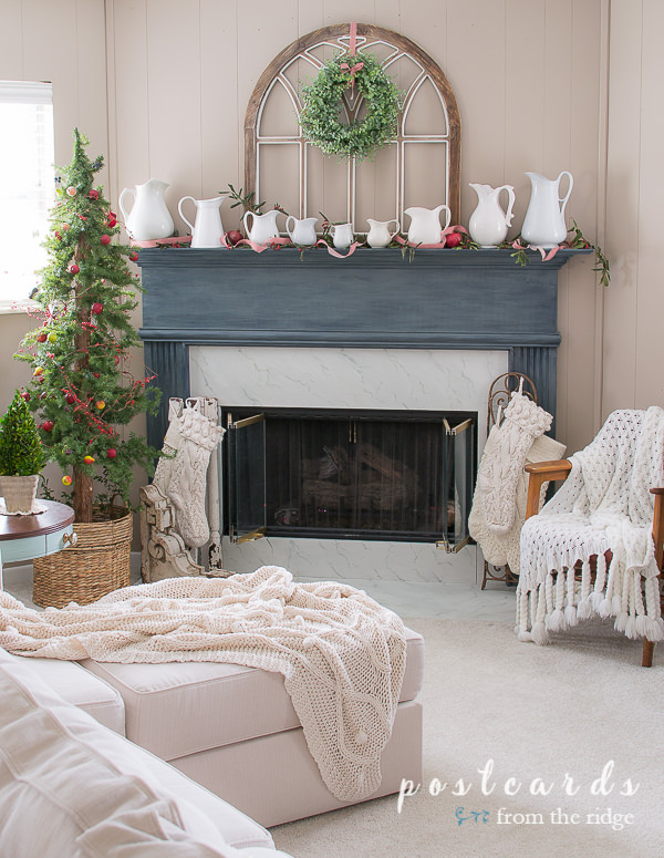 blue mantel with white pitchers and arched wooden window frame
