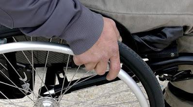Närbild på hand som rullar på hjul på rullstol.