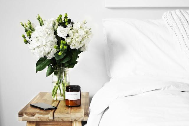 white flowers in a white bedroom, image via unsplash.com
