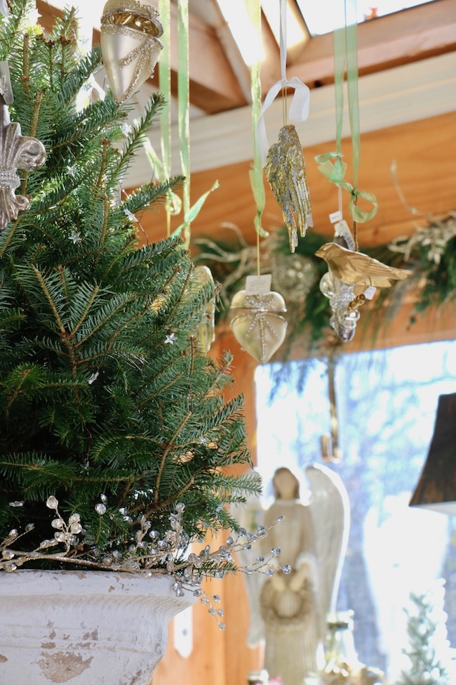 French Country Christmas Event 2019 has several Christmas ornaments hanging around a fresh cut table top tree in a white pedestal urn