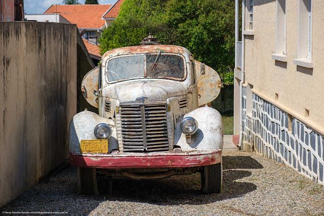 Caminhão tanque antigo estacionado ao lado de uma residência