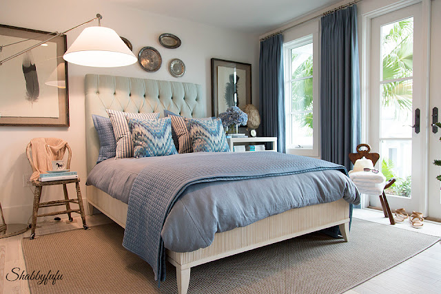 Master bedroom in the HGTV Dream Home 2016 - a bedroom accented with blue; a large upholstered headboard and french doors that lead to the pool.